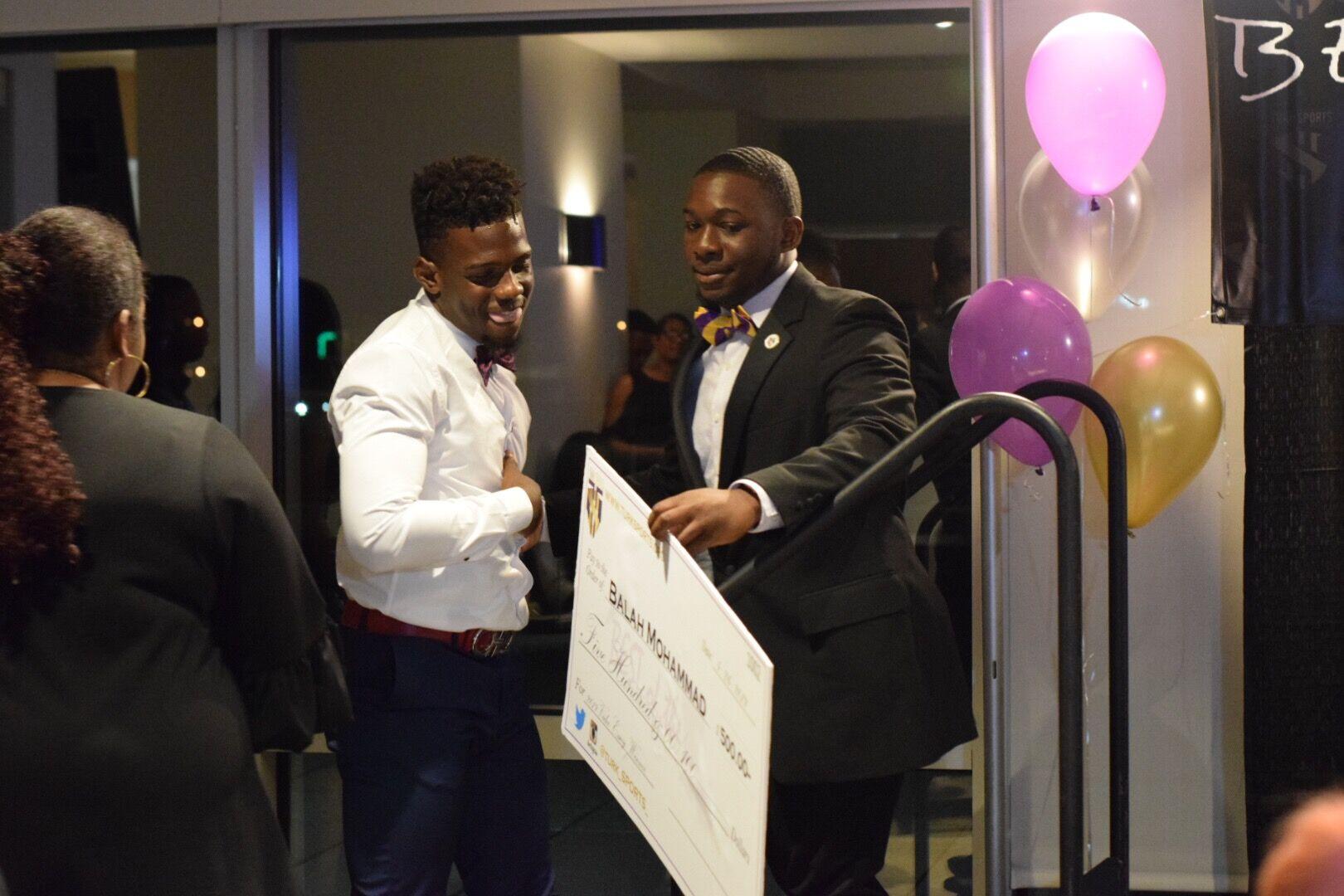 2019 1st Place video essay Winner Balah Muhammad receives check from Lance Jones.