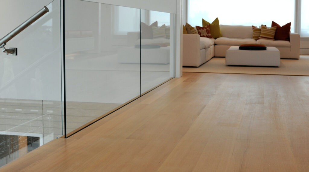 rift and quartered white oak flooring viewing to a living area with a white couch and colorful cushions, to the left is a glass bannister indicating a staircase.