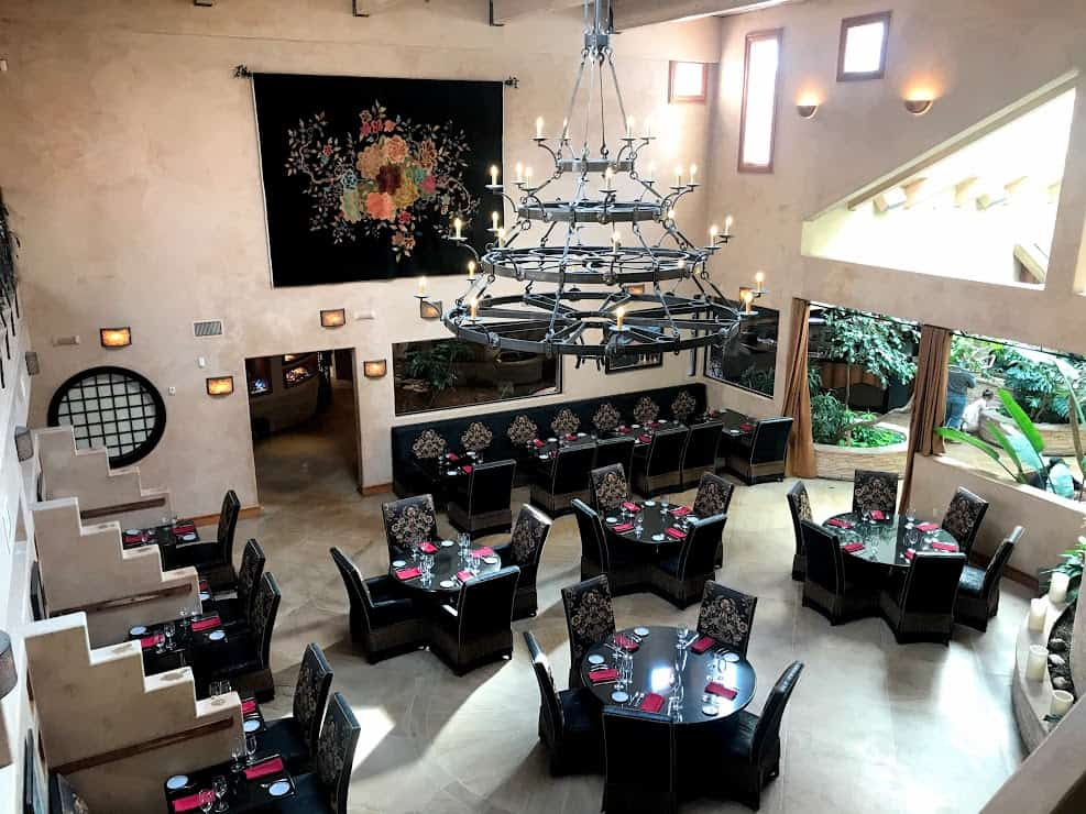 A pueblo style dining room with a wrought iron chandelier and ornate black tables set underneath it