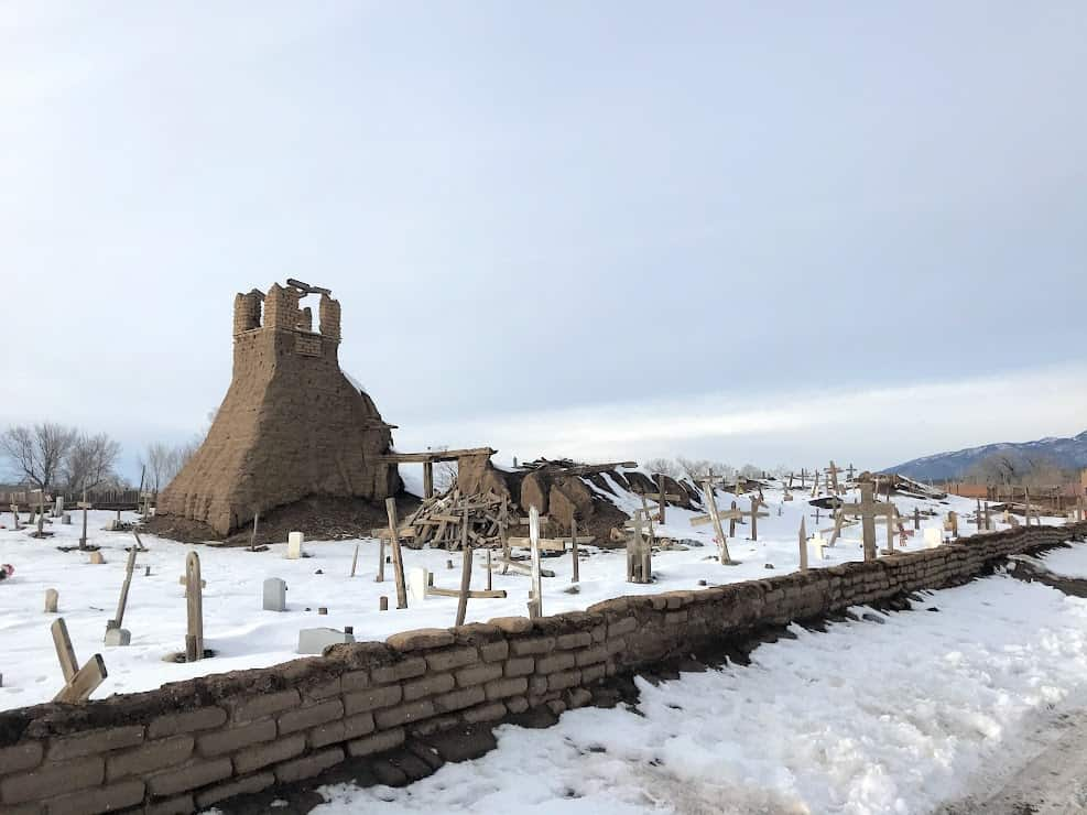 The remains of an adobe church. There is a small adobe brick wall on the border, snow covers the ground of the graveyard, and only the adobe belltower remains.