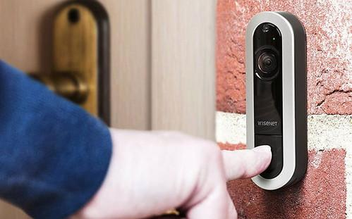 A person pressing a button on a doorbell with a security camera
