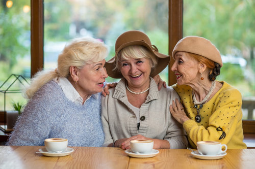 3 older women having a coffee and smiling