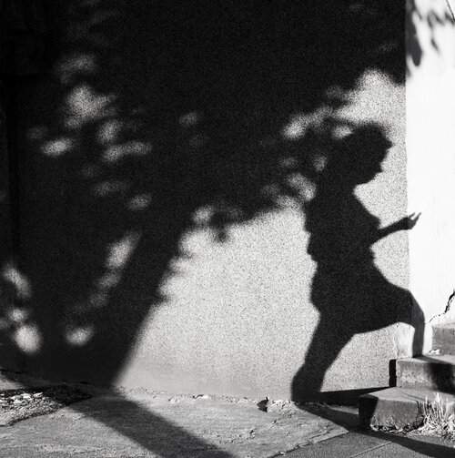 A walking woman's shadow on a wall