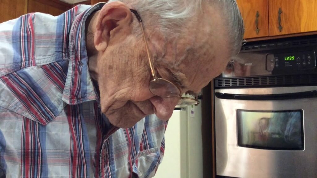 older person with glasses looking down