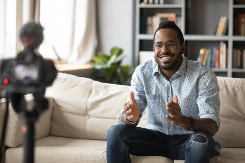 a man sitting on a couch and talking in front of a camera