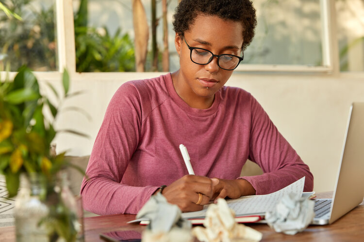 a woman is writing on a paper