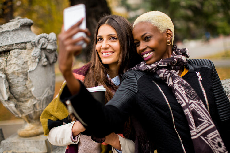 Two women are smiling and taking a photo with a smart phone