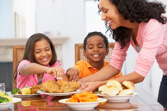 Mother Serving A Meal To Her Children At Home