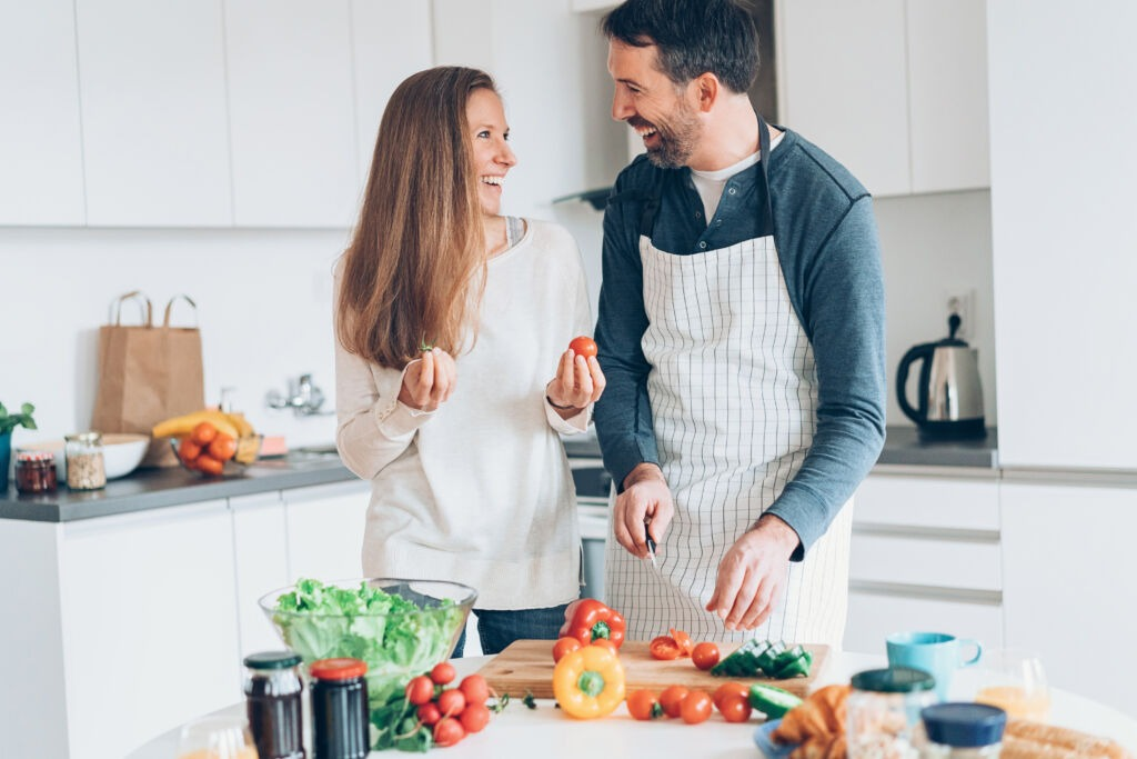 Happy middle aged couple preparing food together