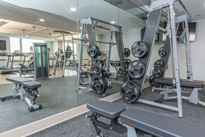Free weights with large mirror in spacious condominium fitness center