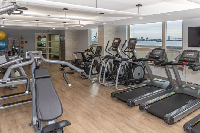 Cardio machines with gorgeous riverfront view in Philadelphia condo fitness center