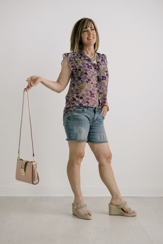 Woman wearing floral blouse with jean shorts