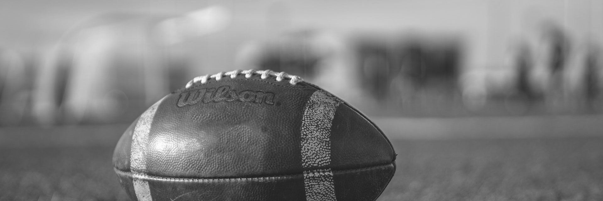 black and white photo of football sitting on field