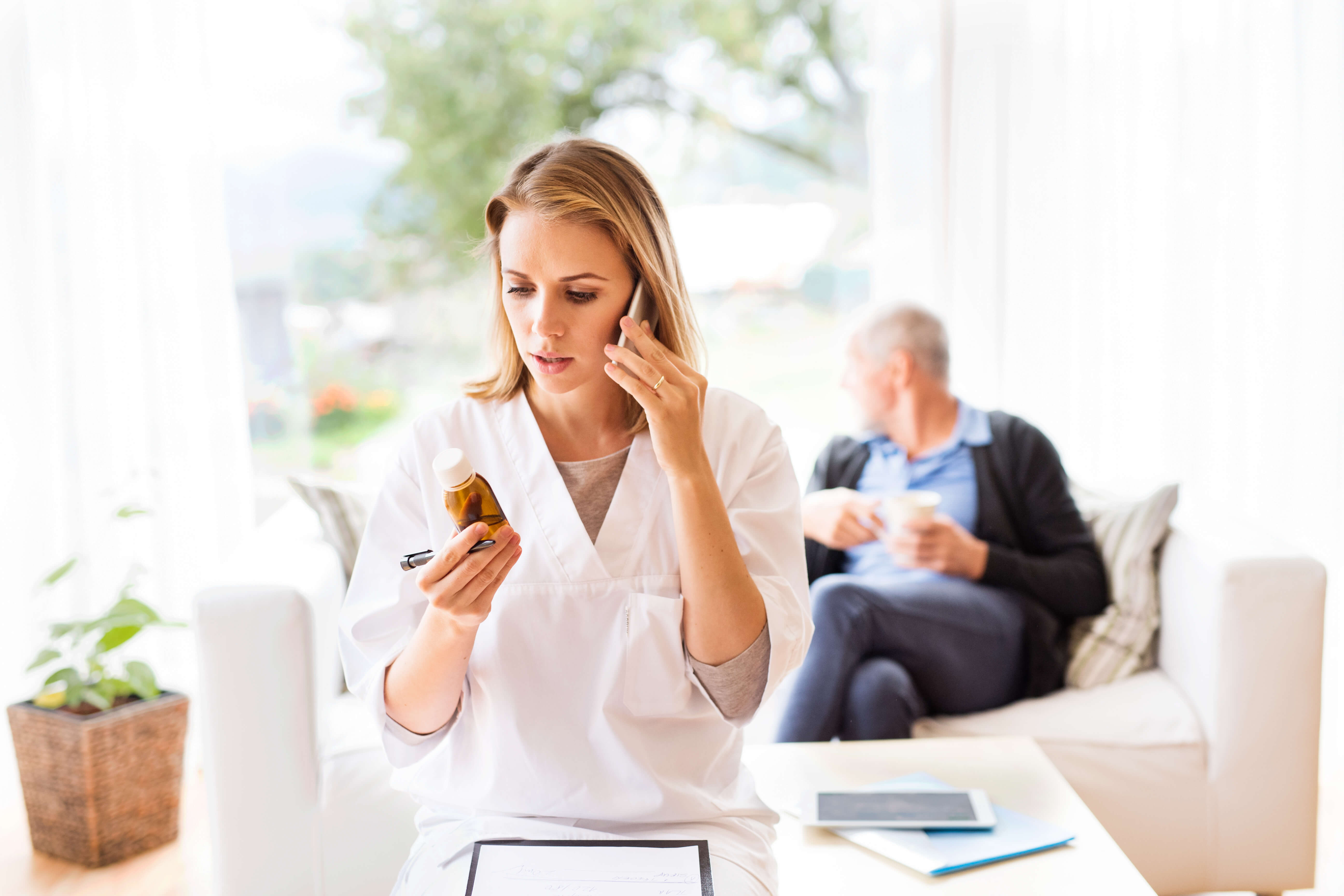 woman bottle man behind plant blonde sofa telephone-triage hospital