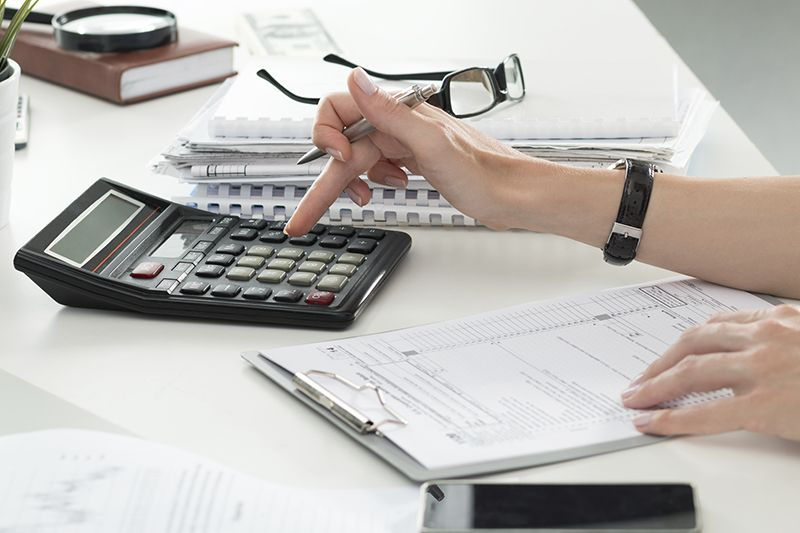 Close up of female accountant or banker making calculations. Savings finances and economy concept cm