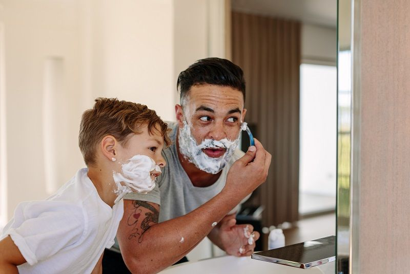 Comp Father and son shaving together in bathroom