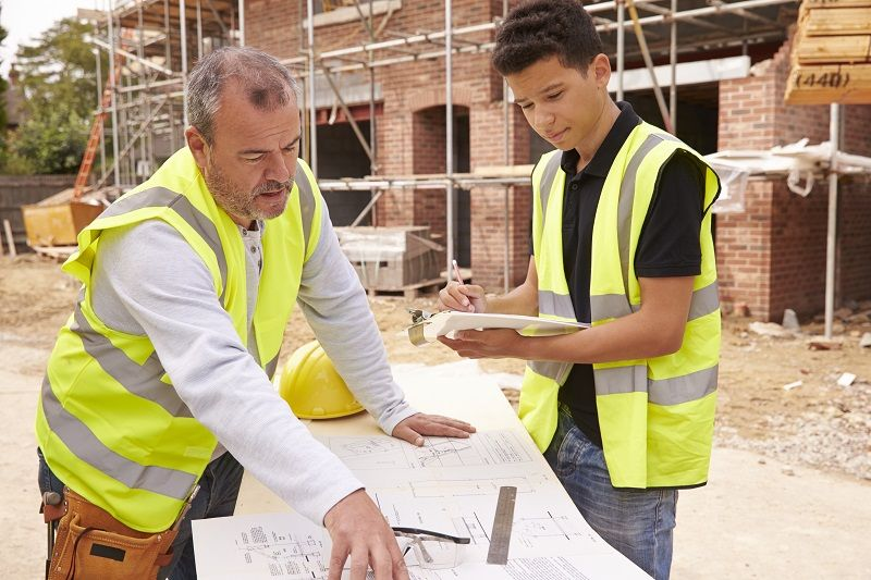 Builder On Building Site Discussing Work With Apprentice cm