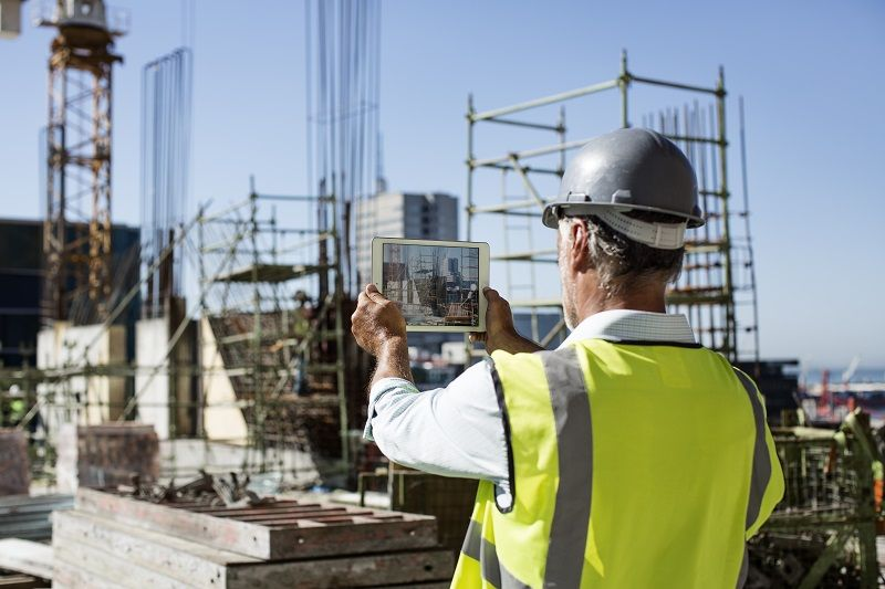 Male architect photographing construction site cm