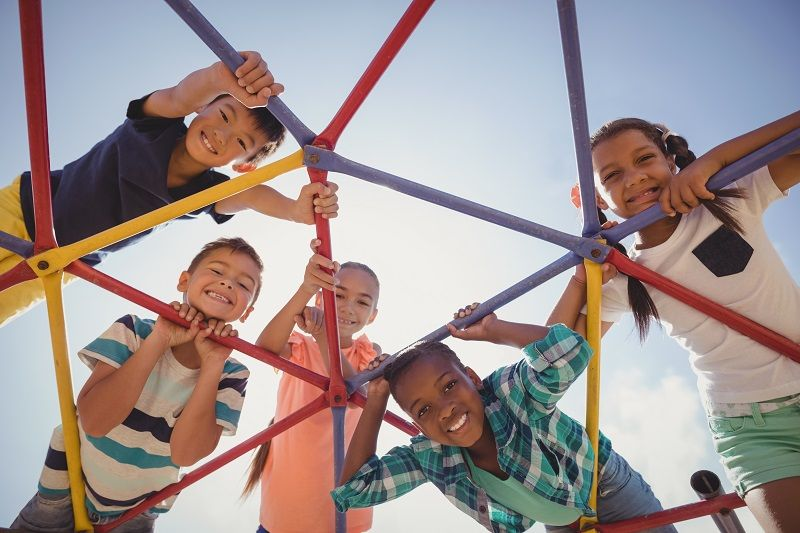 Portrait of happy schoolkids looking through dome climber cm