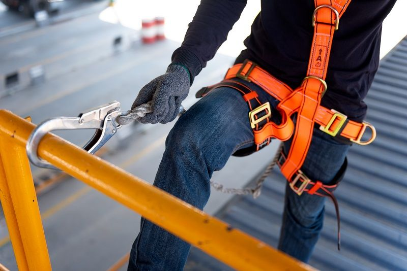 Construction worker use safety harness and safety line working on a new construction site project-cm