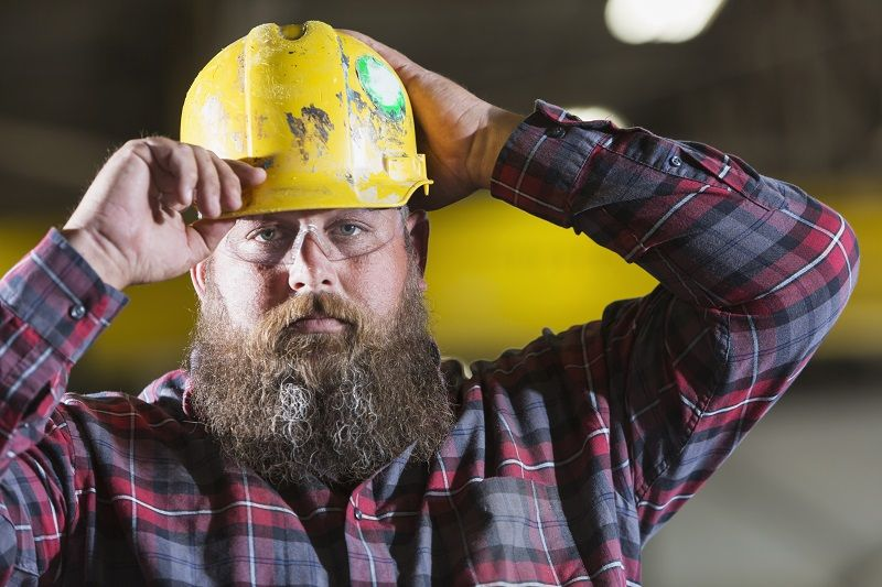 Bearded-construction-worker-putting-on-hardhat