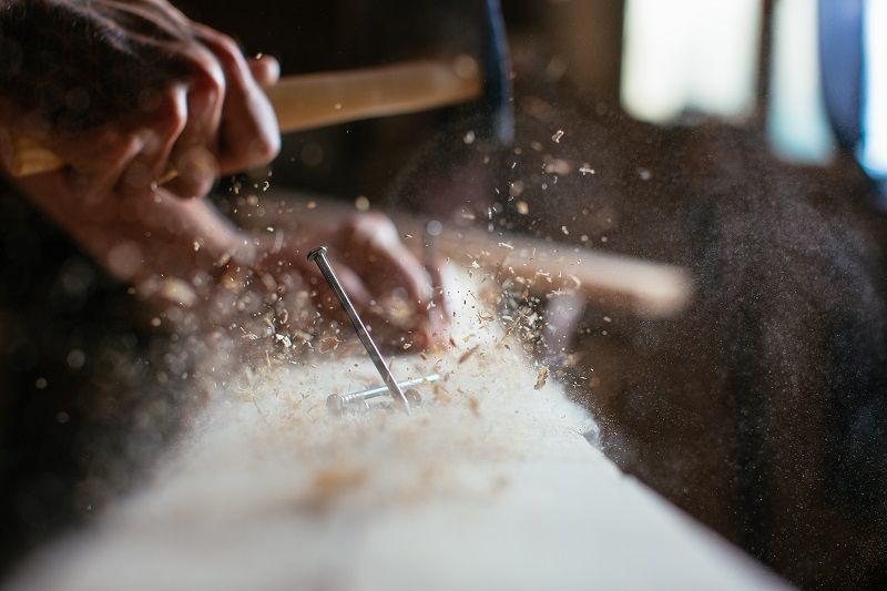 Close-up-of-man-hammering-a-nail-into-wooden-board-cm