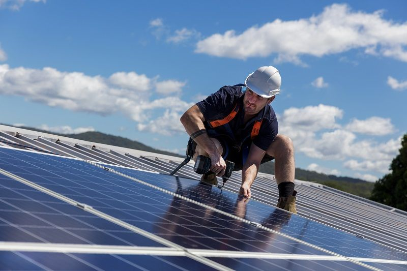 Solar-panel-installer-with-drill-installing-solar-panels-cm