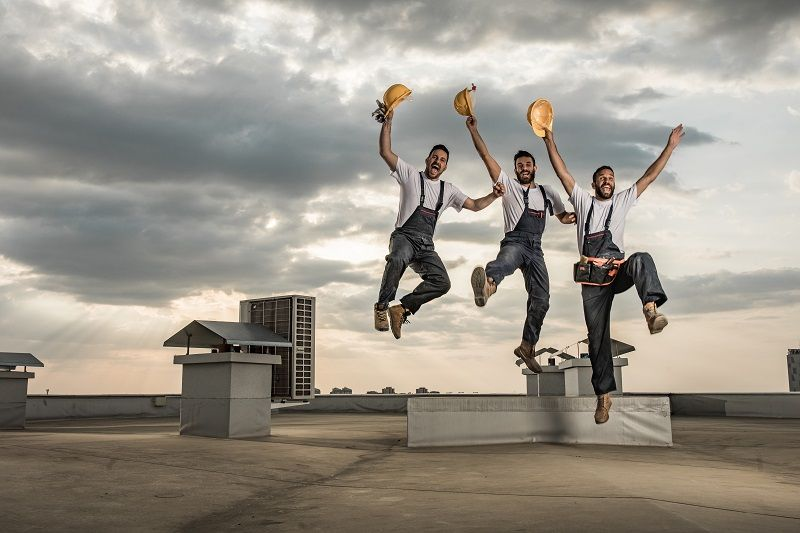 Team-of-playful-manual-workers-having-fun-while-jumping-on-a-roof.-cm