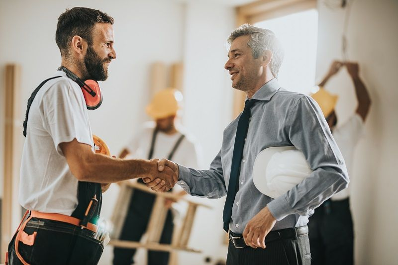 Happy-manual-workers-shaking-hands-with-an-architect-at-construction-site-cm