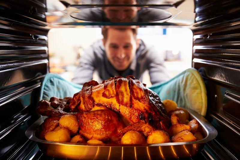 Man-Taking-Roast-Turkey-Out-Of-The-Oven-cm
