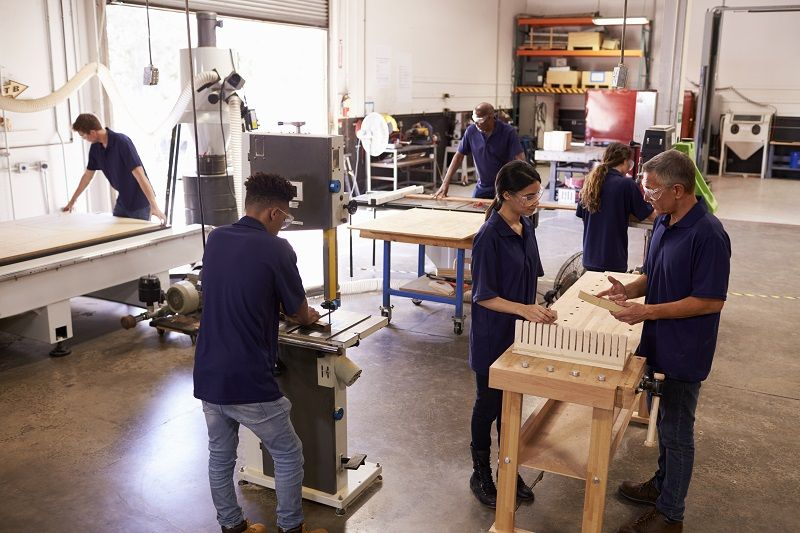 Carpenters-Working-On-Machines-In-Busy-Woodworking-Workshop-cm