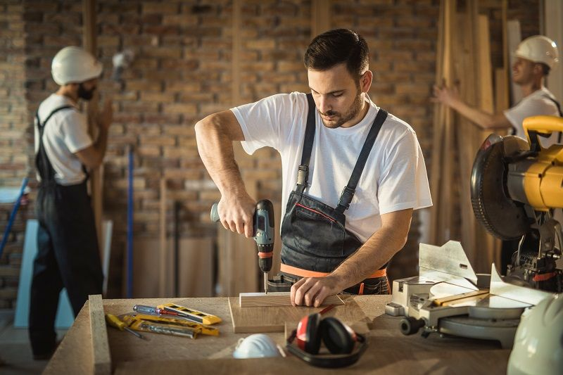 Manual-worker-using-drill-while-making-home-improvements-on-construction-site-cm