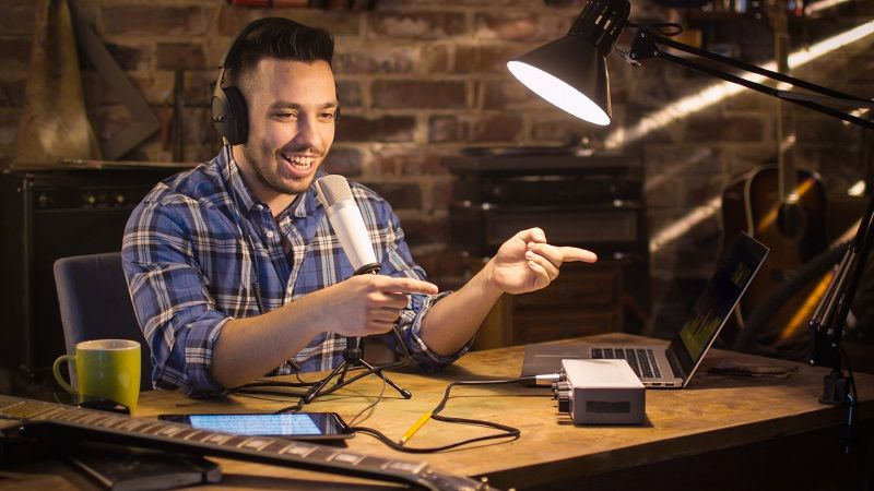 Young-man-makes-a-podcast-audio-recording-at-home-in-a-garage-cm