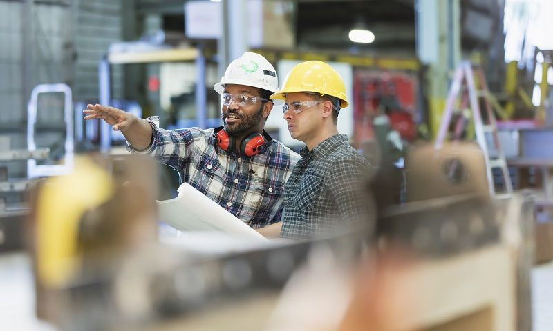 Multi-ethnic-workers-talking-in-metal-fabrication-plant--cm