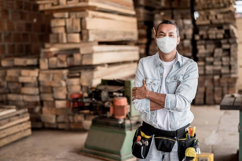 Carpenter working at his workshop wearing a facemask to avoid coronavirus-cm