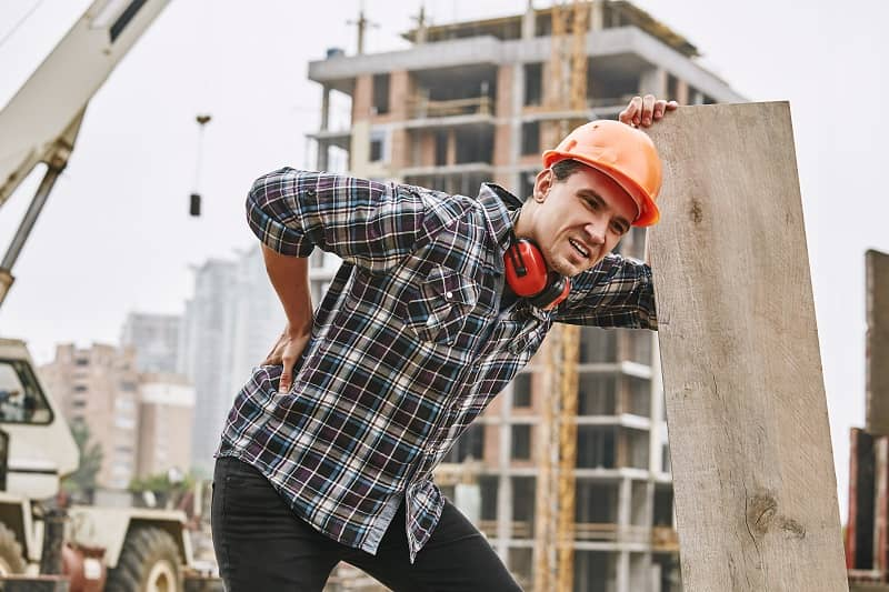 Hard work. Construction worker in protective helmet feeling back pain while working at construction site. Building construction. Pain concept-cm