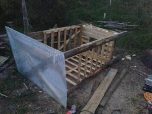 """Préparation au sol d'une cabine déplaçable, pour former des buttes de culture. Ici avec une """"caisse"""" récupérée en jardinerie, des dosses et bois de récup. La palette a été percée, et renforcée."""