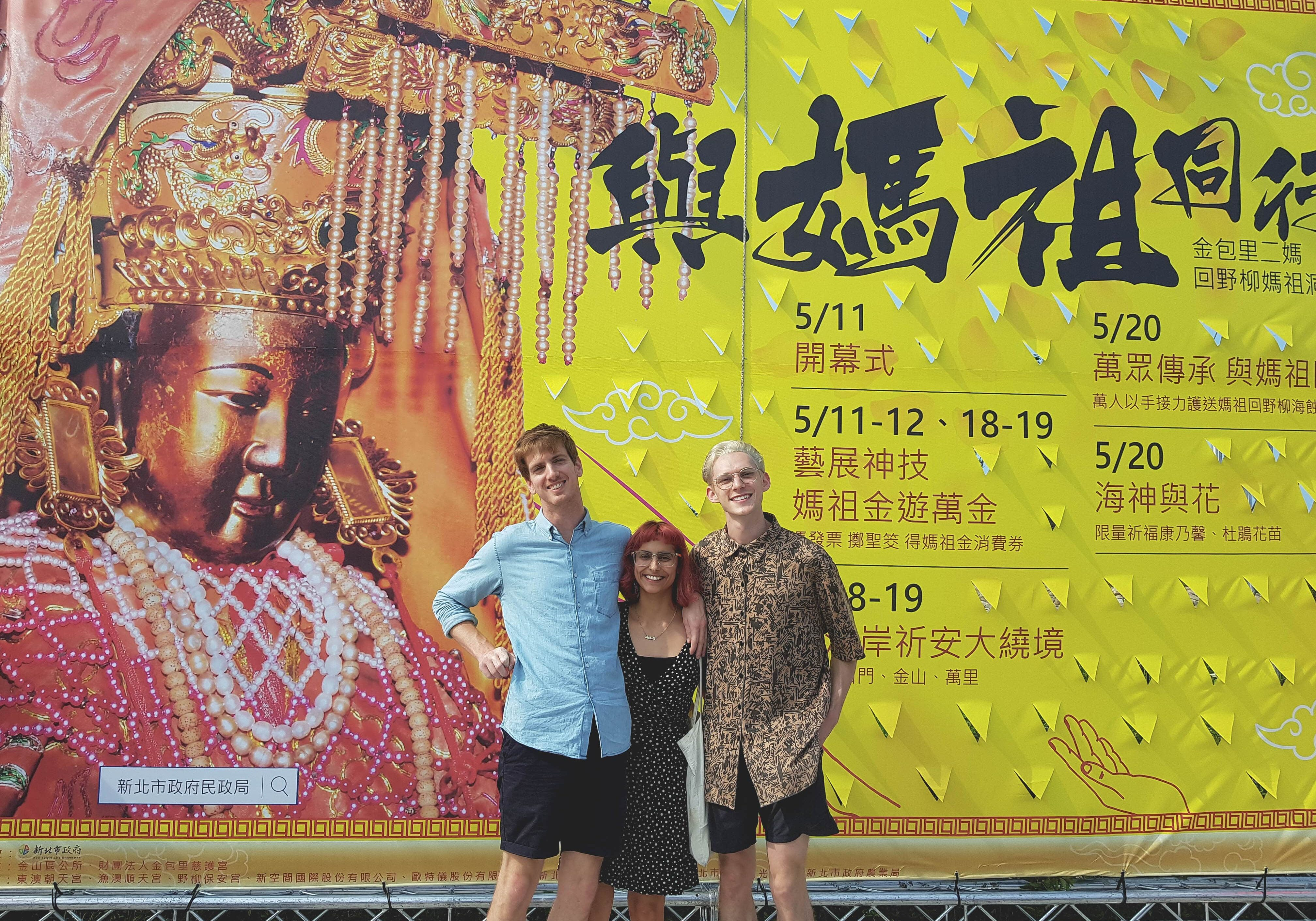 Peter, Michelle and Taylor in front of Mazu Goddess Festival poster.