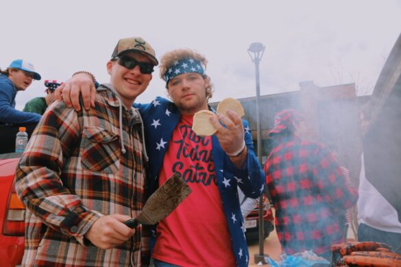 Seniors Will Norris and Jaden Schimke grilled hot dogs and hamburgers at the America station. Parking a truck and blasting country music outside of the main entrance, the booth isn't culturally enlightening but rather a senior tradition.