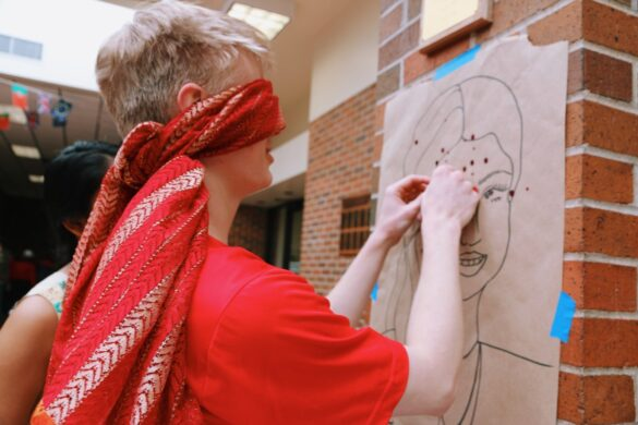 """Senior Sarvika Mahto led students to """"pin the dot"""" on an Indian woman's forehead. Mahto ran the Indian booth alongside senior Kanchan Hans and also participated in the Indian dance Tuesday."""