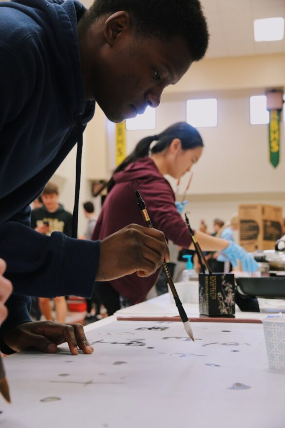 Junior Leke Oduwole paints a Chinese character in exchange for a fortune. Senior Anna Xu, who ran the booth, created this challenge as an incentive to learn more about Chinese culture, rather than just taking food and going.
