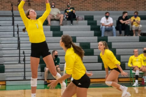 Sophomore Ella Swindle sets a ball as senior Emma Roush prepares to jump for the spike at the girls' volleyball Tuesday, Sept. 8. Photo by Ana Manzano.