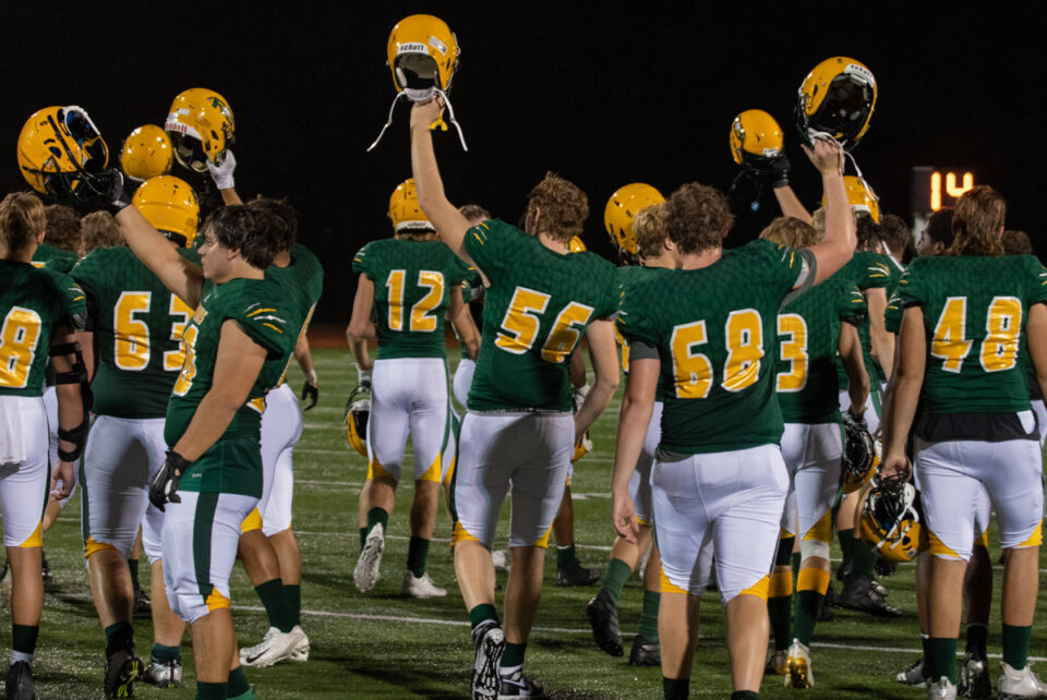 The RBHS football team raise their helmets in celebration after winning against JCHS on Friday, Sept. 11. Photo by Ana Manzano.
