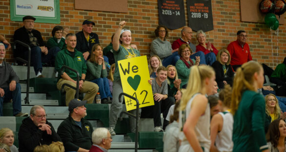 Junior Maggie Campbell holds a handmade sign cheering on number 12 (Senior guard Samantha McKinley) at the girls' basketball game Thursday, Jan. 20. Photo by Ana Manzano.