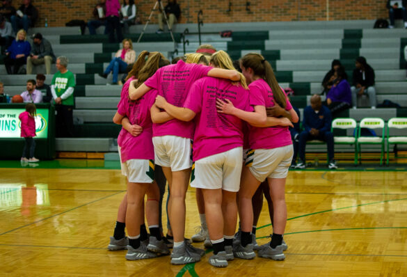 The varsity girls' basketball team stands in a team huddle during their pink-out game Wednesday, Feb. 19. Photo by Ana Manzano.