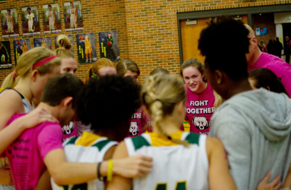 Before they stepped onto the court, the girls' basketball team participated in a team huddle along with their coaches Wednesday, Feb. 19. Photo by Ana Manzano.