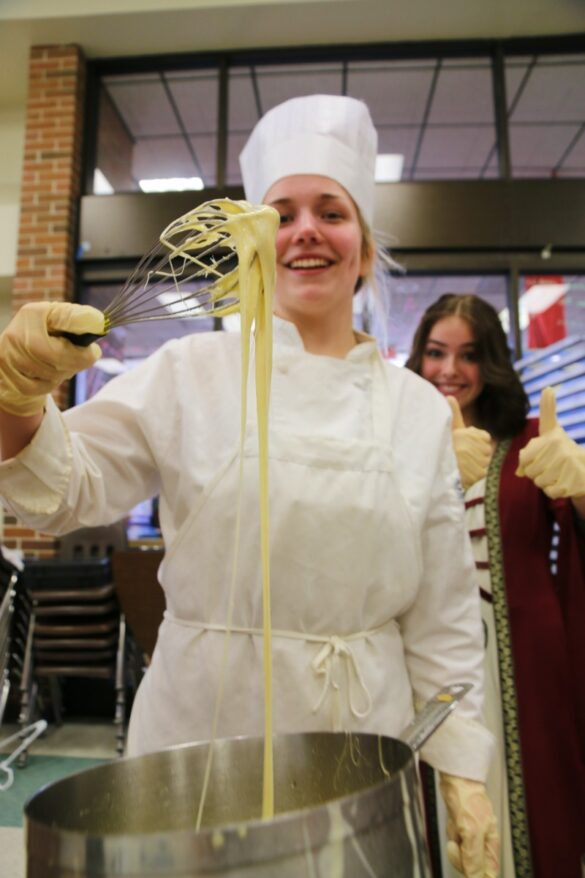 Sophomore Olivia Hayes lifts cheese fondue with her whisk. Hayes represented Italy for her Columbia Area Career Center culinary class.