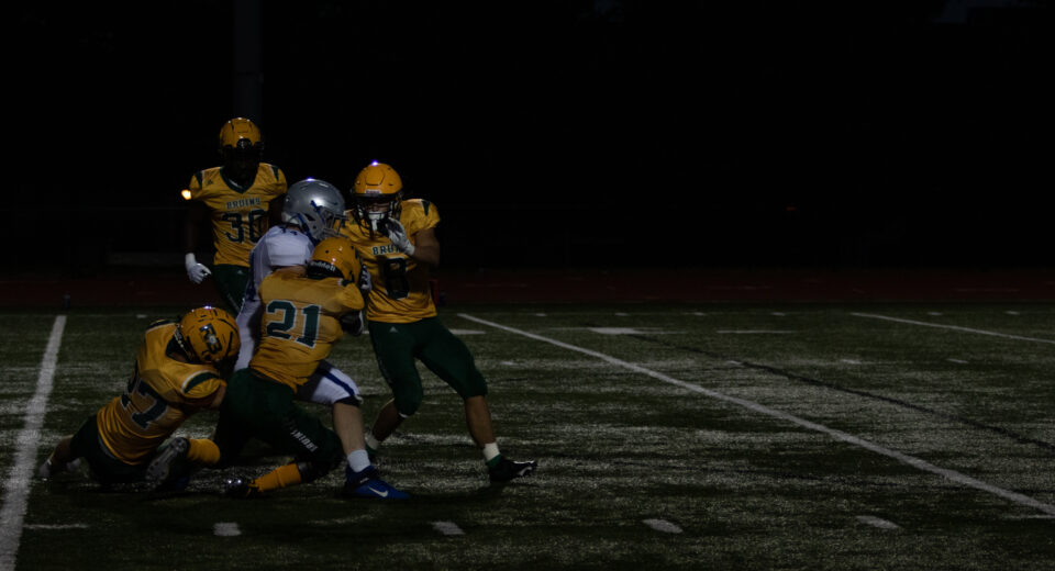 Bruins defenders attempt to stop the cavaliers' running back from scoring a touchdown. The defense struggled to contain the cavaliers' running game and gave up 49 points. Photo by Parker Boone.