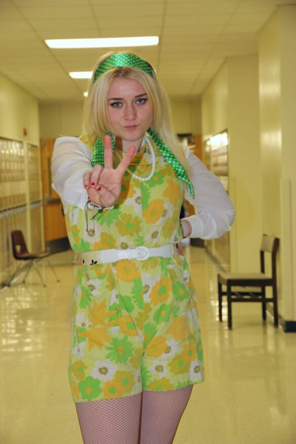 Junior Nora Croom pouts and holds a peace sign on her way to class 3rd hour. Her flower-child 60's inspired outfit comes from the theater costume closet, as she is close with the costumer of the choir program.