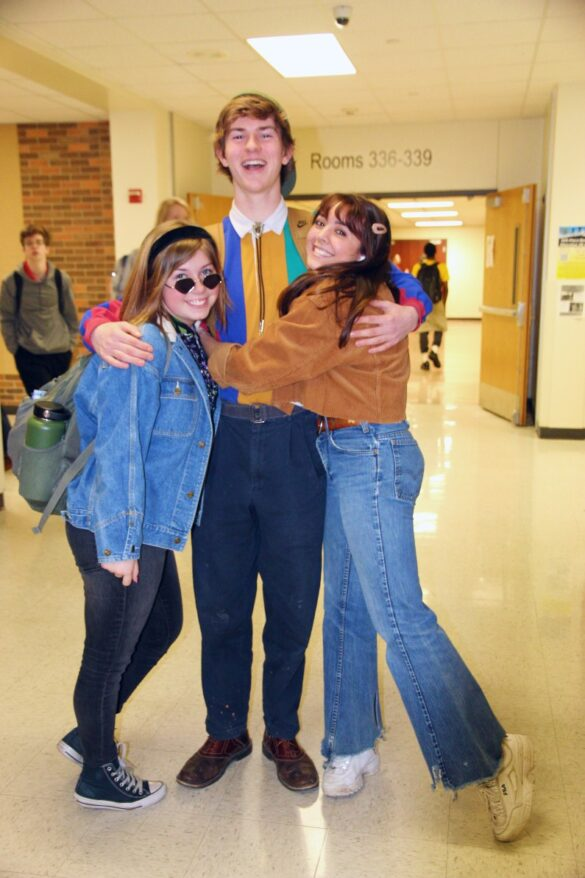 Students Sophia Guess and Adrienne Walker hug senior Luke in the hallway, excited to see their friends dressing up too